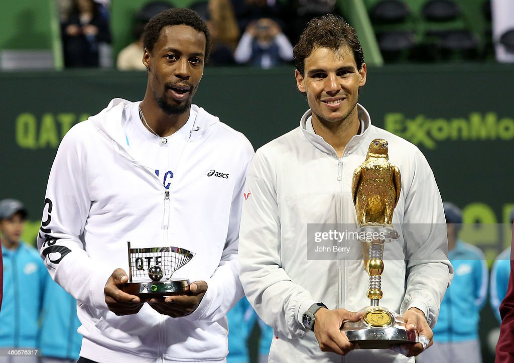 Finalist Gael Monfils of France and winner Rafael Nadal of Spain pose during the trophy ceremony after the final of the Qatar ExxonMobil Open 2014...