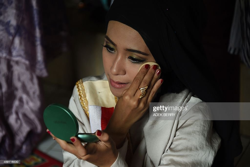 Finalist of the 2014 World Muslimah Awards Elis Sholihah retouches her makeup after prayer in Yogyakarta on November 17 2014 Indonesia hosted the 4th...