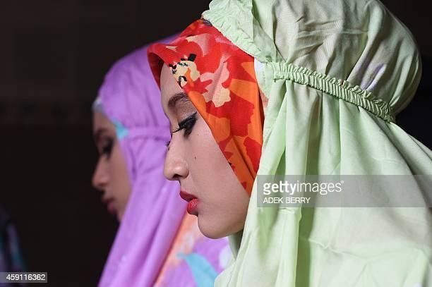 Finalists of the 2014 World Muslimah Awards Gesti Nur Ula Derapati of Indonesia and Molina Ulfah Ramadhan of Indonesa pray in Yogyakarta on November...