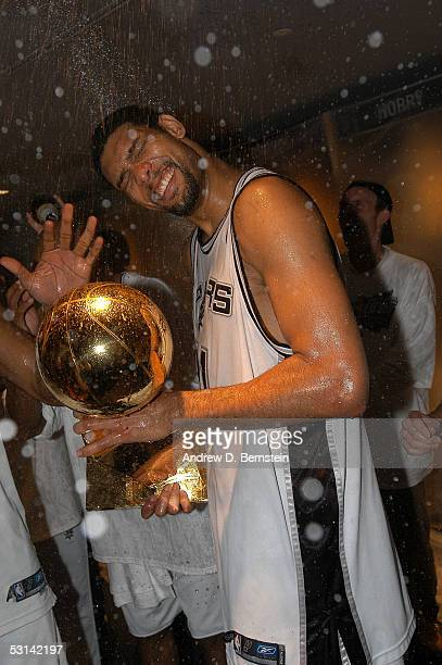 Finals MVP Tim Duncan of the San Antonio Spurs celebrates with Larry O'Brien trophy in the locker room as he is sprayed with champagne following the...