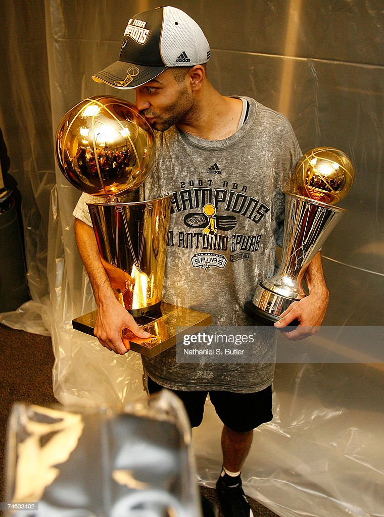 Finals MVP Tony Parker #9 the San Antonio Spurs celebrates in the locker with the Larry O'Brien Championship trophy and his MVP trophy after their 83-82 win against the Cleveland Cavaliers in Game Four of the NBA Finals at the Quicken Loans Arena on June 14, 2007 in Cleveland, Ohio.