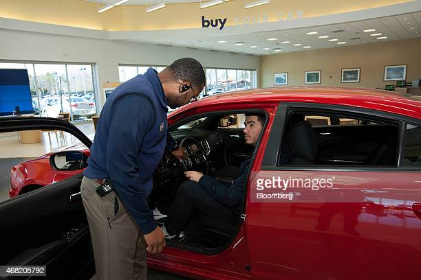 Finance and sales manager Warren Cox left speaks with a customer about a Dodge Charger at a CarMax Inc dealership in Brandywine Maryland US on Sunday...