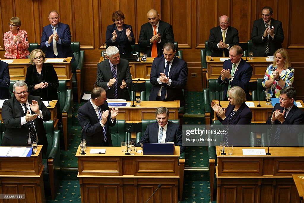 Finance Minister Bill English is applauded by Prime Minister John Key and fellow National MPs after delivering the 2016 budget presentation at...
