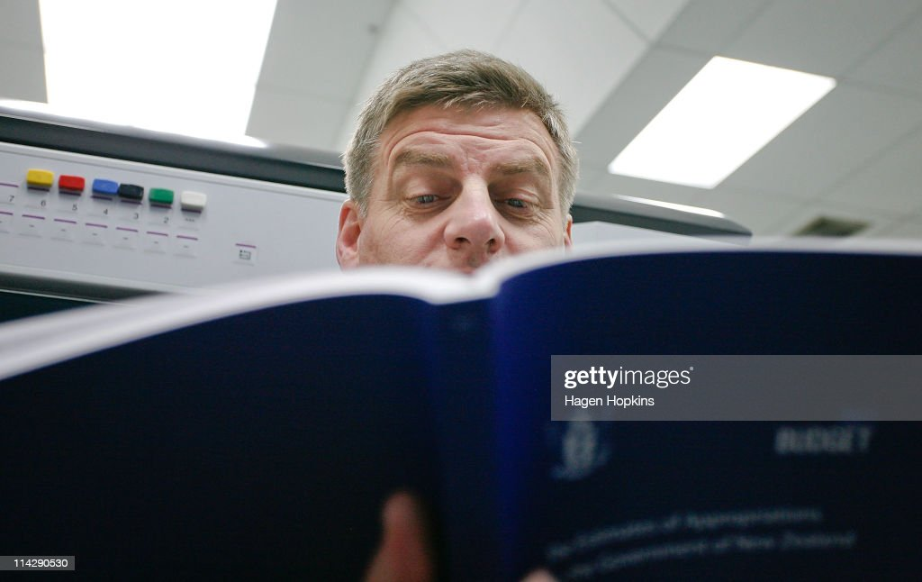 Finance Minister Bill English reads a copy of the 2011 budget at Printlink during the printing of the budget on May 18 2011 in Wellington New Zealand...