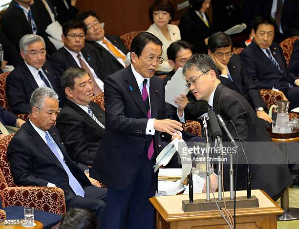Finance Minister Taro Aso is helped by a secretary while addressing duirng the upper house budget committee at the diet building on January 19 2016...