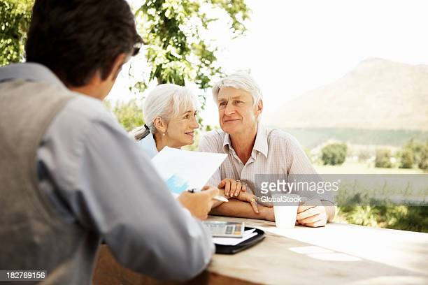 Financial advisor - Banking agent sitting with senior client