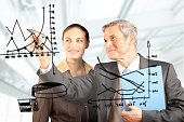 A financial advisor drawing a graph on a glass board
