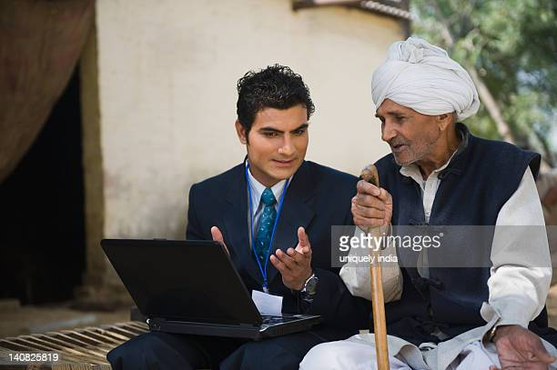 Financial advisor explaining to a farmer about agriculture loan, Hasanpur, Haryana, India