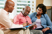 Financial Advisor Talking To Senior Couple At Home Signing Documents Sitting On Sofa