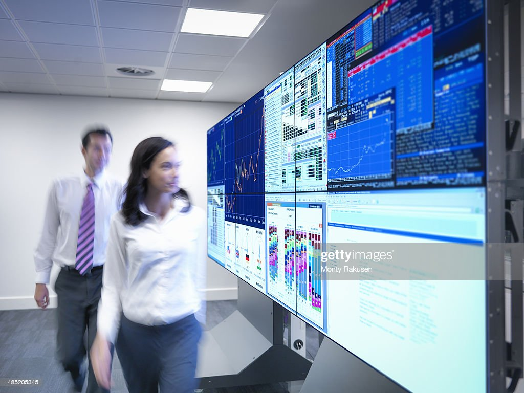 Financial analysts looking at screens in control room