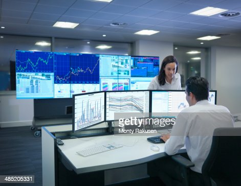 Financial analysts working with graphs on screens in control room
