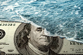 close up shotof water covering one hundered dollar bill