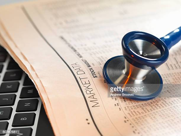 Financial health check: stethoscope on newspaper with financial markets for investing