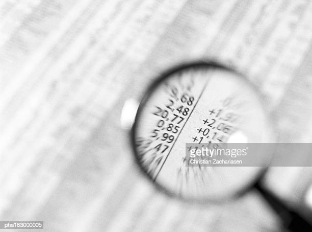 Financial numbers under magnifying glass, close-up, b&w