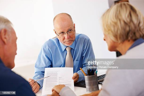 Financial planner showing a form to senior couple