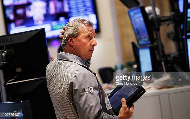 A financial professional looks up at a screen on the floor of the New York Stock Exchange at the end of the trading day March 4 2011 in New York City...