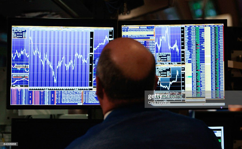 A financial professional loosk at his computer screen on the floor of the New York Stock Exchange at the end of the trading day December 16 2008 in...