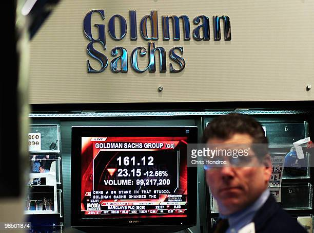 A financial professional works in the Goldman Sachs booth on the floor of the New York Stock Exchange while a television reports airs about the...
