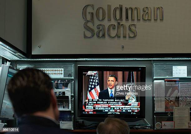 Financial professionals in the Goldman Sachs booth on the floor of the New York Stock Exchange at midday watch President Obama give a speech about...
