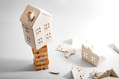Financial risk, unstable real estate investment and shaky housing market concept with a home on stacked wooden building blocks surrounded by the ruins and debris of another house that collapsed