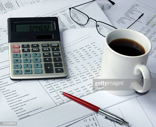 Financial spreadsheets and calculator on accountant's desk