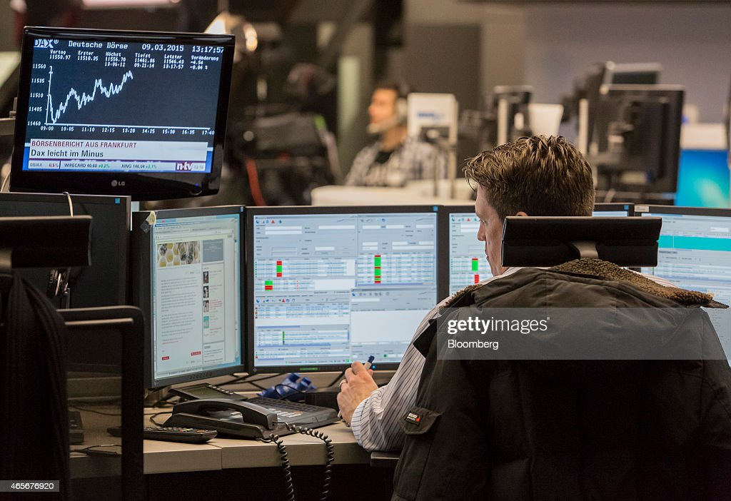 A financial trader monitors data on computer screens as the DAX Index curve is displayed at the Frankfurt Stock Exchange in Frankfurt Germany on...