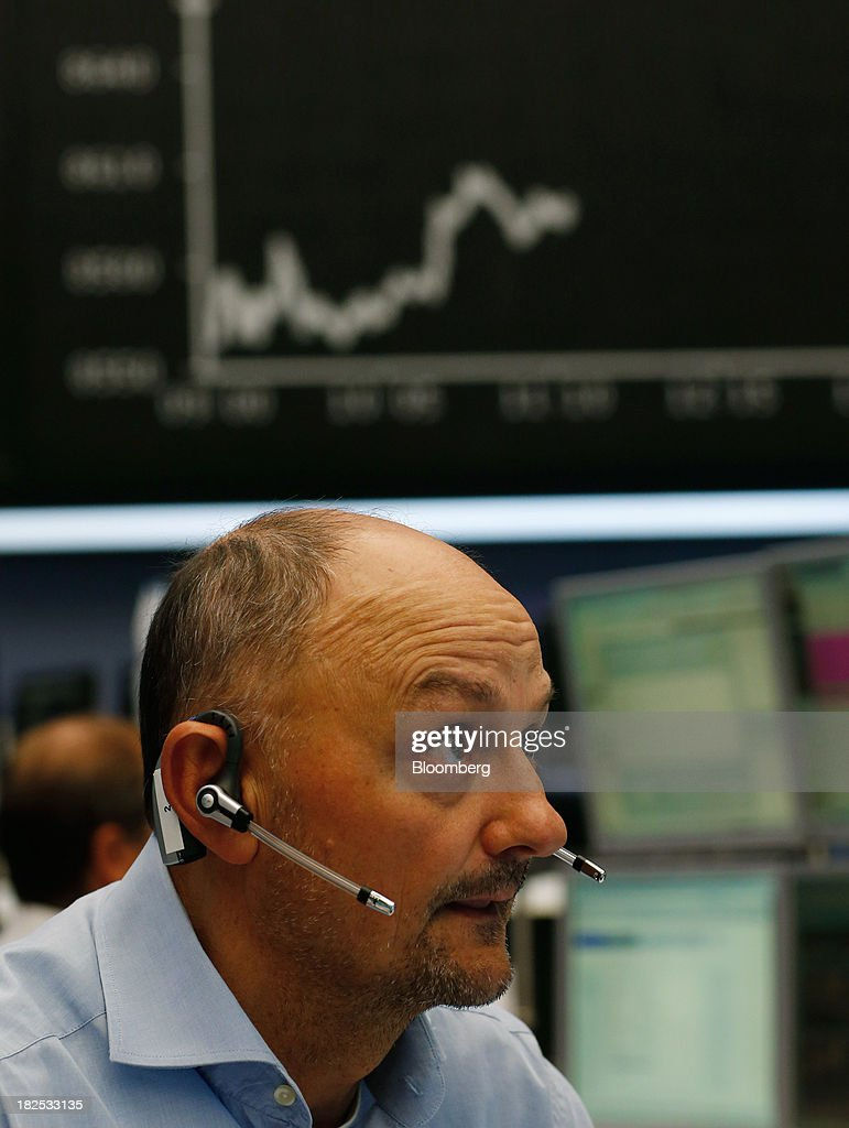 A financial trader monitors data on computer screens at the Frankfurt Stock Exchange in Frankfurt, Germany, on Monday, Sept. 30, 2013. Global stocks fell, trimming their biggest quarterly gain since the start of 2012, while the Japanese yen strenghtened before a potential U.S. government shutdown. Photographer: Ralph Orlowski/Bloomberg via Getty Images