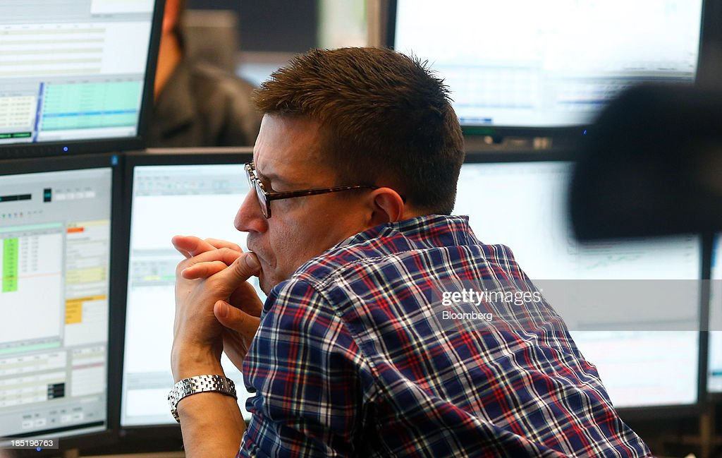 A financial trader monitors data on computer screens at the Frankfurt Stock Exchange in Frankfurt, Germany, on Friday, Oct. 18, 2013. Global stocks rose for a third day, extending a five-year high, and copper climbed after China's economic growth quickened. Photographer: Ralph Orlowski/Bloomberg via Getty Images