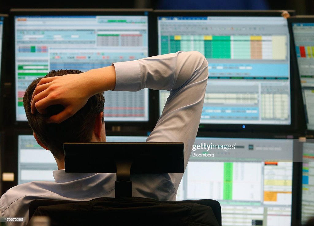 A financial trader monitors data on computer screens at the Frankfurt Stock Exchange in Frankfurt, Germany, on Thursday, Feb. 20, 2014. Deutsche Boerse AG plans to set up a clearinghouse in Singapore to compete with Singapore Exchange Ltd. and IntercontinentalExchange Group Inc. as the owner of the Frankfurt Stock Exchange and the Eurex futures market seeks to benefit from new financial regulations. Photographer: Ralph Orlowski/Bloomberg via Getty Images
