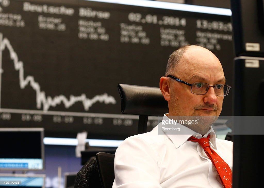 A financial trader monitors data on computer screens beneath a display of the DAX Index curve at the Frankfurt Stock Exchange in Frankfurt, Germany, on Thursday, Jan. 2, 2014. Most German stocks fell on the first day of trading in 2014, following an annual gain for the benchmark DAX Index, as data showed manufacturing in Europe's largest economy expanded for a sixth month. Photographer: Ralph Orlowski/Bloomberg via Getty Images