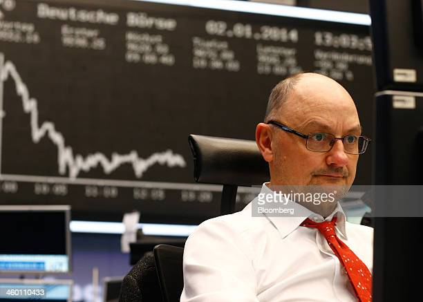 A financial trader monitors data on computer screens beneath a display of the DAX Index curve at the Frankfurt Stock Exchange in Frankfurt Germany on...