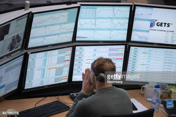 A financial trader monitors data on computer screens on the trading floor inside the Amsterdam Stock Exchange operated by Euronext NV in Amsterdam...