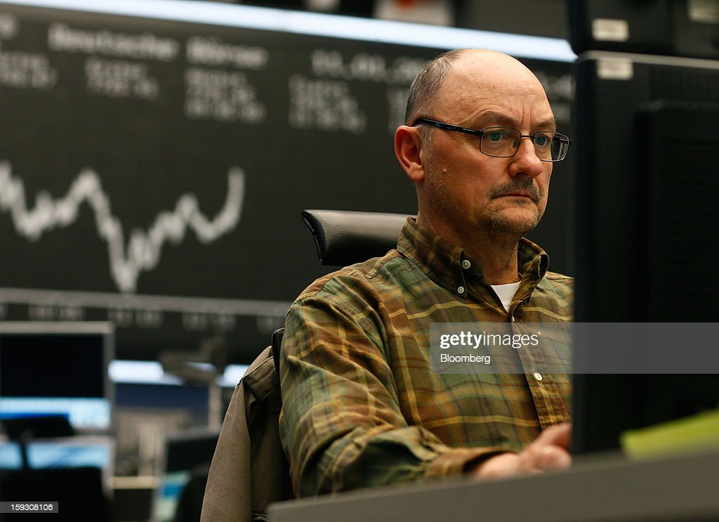 A financial trader monitors data on his computer screens in front of a display of the DAX Index curve at the Frankfurt Stock Exchange in Frankfurt, Germany, on Friday, Jan. 11. 2013. European stocks pared their decline as Italy's borrowing costs dropped at a debt sale, offsetting concern that China has less room for monetary easing after a reported showed inflation increased more than estimated. Photographer: Ralph Orlowski/Bloomberg via Getty Images