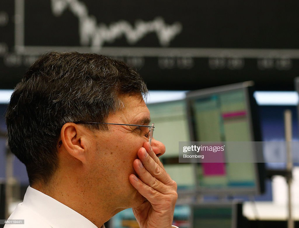 A financial trader reacts as the DAX Index curve is seen beyond at the Frankfurt Stock Exchange in Frankfurt, Germany, on Thursday, Jan. 2, 2014. Most German stocks fell on the first day of trading in 2014, following an annual gain for the benchmark DAX Index, as data showed manufacturing in Europe's largest economy expanded for a sixth month. Photographer: Ralph Orlowski/Bloomberg via Getty Images