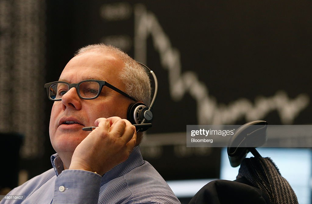 A financial trader speaks into a telephone headset as the DAX Index curve is seen beyond at the Frankfurt Stock Exchange in Frankfurt, Germany, on Thursday, Jan. 2, 2014. Most German stocks fell on the first day of trading in 2014, following an annual gain for the benchmark DAX Index, as data showed manufacturing in Europe's largest economy expanded for a sixth month. Photographer: Ralph Orlowski/Bloomberg via Getty Images