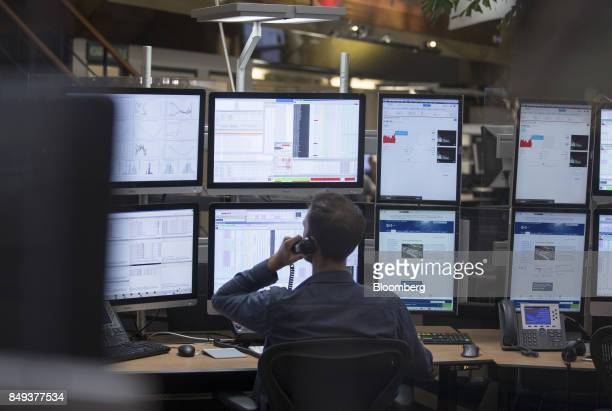 A financial trader speaks on a fixed line telephone while monitoring data on computer screens on the trading floor inside the Amsterdam Stock...