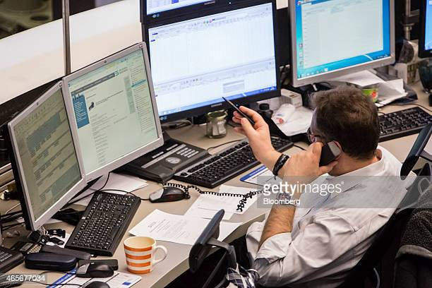 A financial trader speaks on a fixed lined telephone as he monitors data on computer screens at the Frankfurt Stock Exchange in Frankfurt Germany on...
