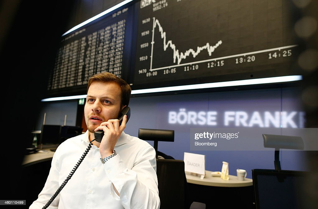 A financial trader speaks on a telephone beneath a display of the DAX Index curve at the Frankfurt Stock Exchange in Frankfurt, Germany, on Thursday, Jan. 2, 2014. Most German stocks fell on the first day of trading in 2014, following an annual gain for the benchmark DAX Index, as data showed manufacturing in Europe's largest economy expanded for a sixth month. Photographer: Ralph Orlowski/Bloomberg via Getty Images