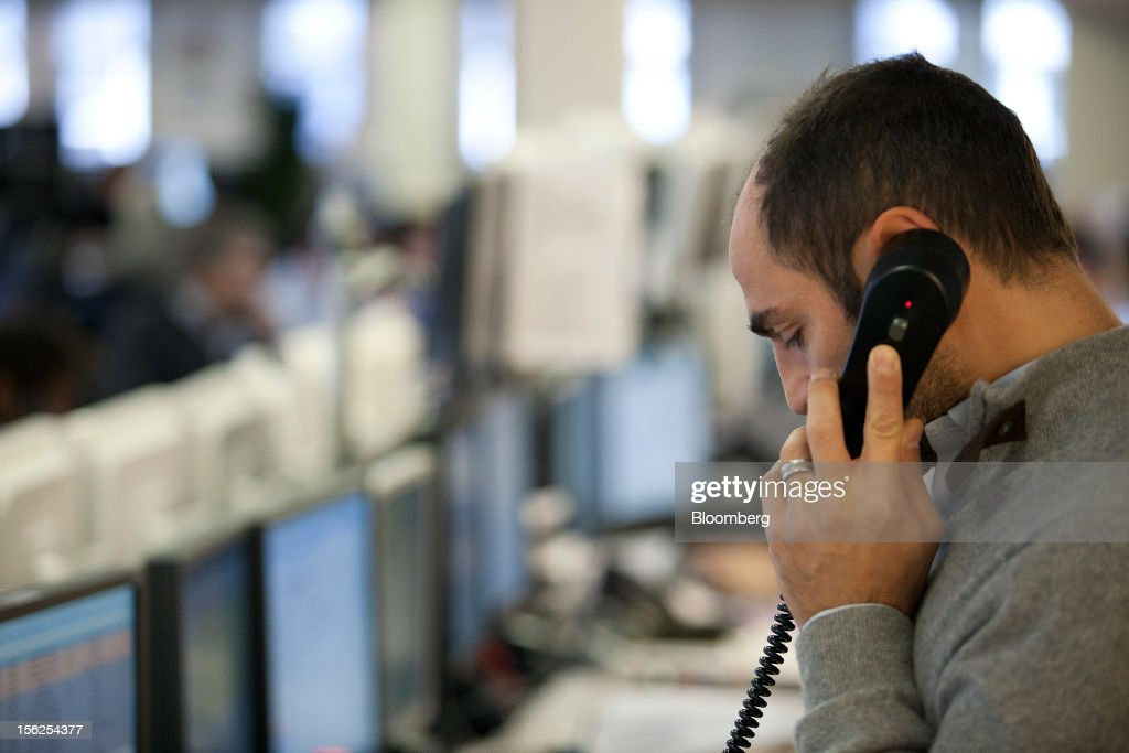 A financial trader speaks on the telephone as he monitors trading information displayed on his computer screens at Aurel BGC's brokerage in Paris, France, on Monday, Nov. 12, 2012. European stocks fluctuated between gains and losses as finance ministers prepared to discuss Greek aid after the country's lawmakers approved the 2013 budget. Photographer: Balint Porneczi/Bloomberg via Getty Images