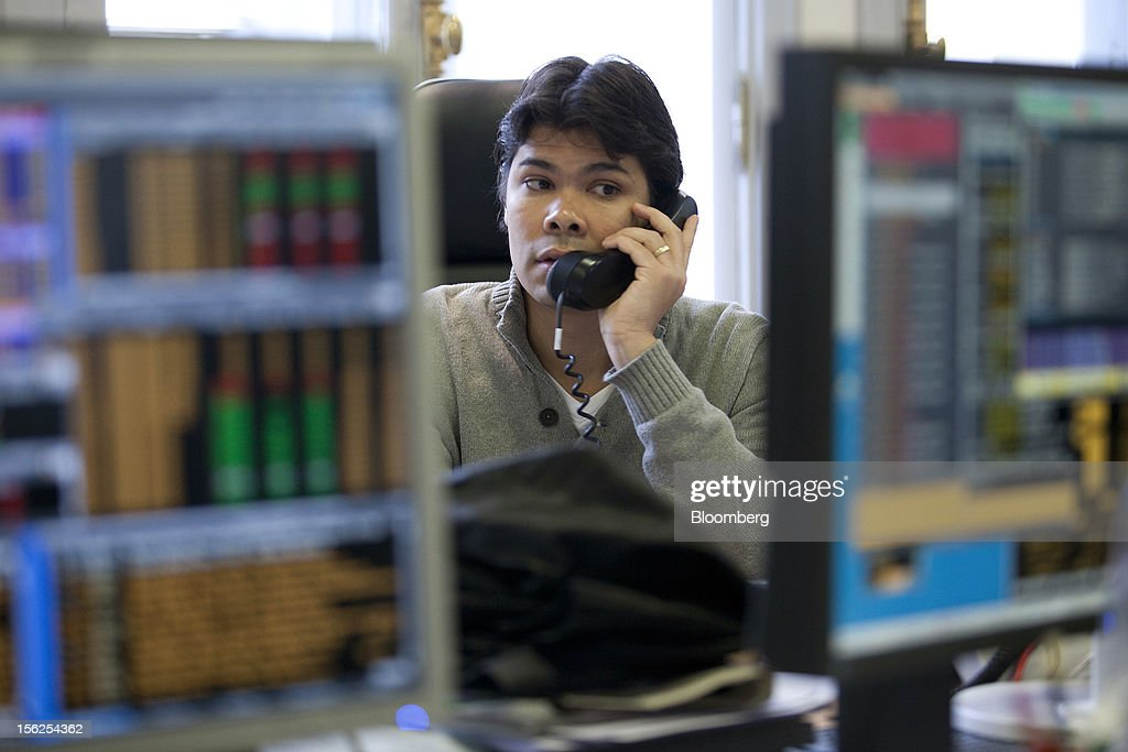A financial trader speaks on the telephone as he works at the Aurel BGC brokerage in Paris, France, on Monday, Nov. 12, 2012. European stocks fluctuated between gains and losses as finance ministers prepared to discuss Greek aid after the country's lawmakers approved the 2013 budget. Photographer: Balint Porneczi/Bloomberg via Getty Images