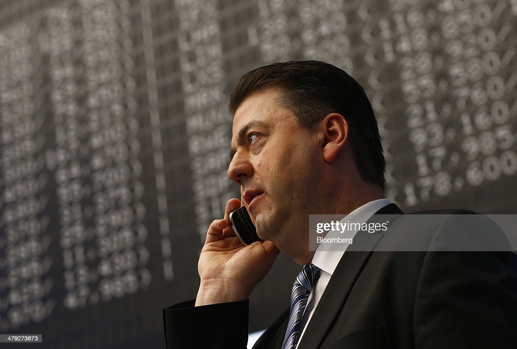 A financial trader uses a mobile phone as he works at the Frankfurt Stock Exchange in Frankfurt, Germany, on Monday, March 17, 2014. European stocks advanced, following their biggest weekly drop since January, as companies from RWE AG to Vodafone Group Plc rose amid renewed merger-and-acquisition activity. Photographer: Ralph Orlowski/Bloomberg via Getty Images