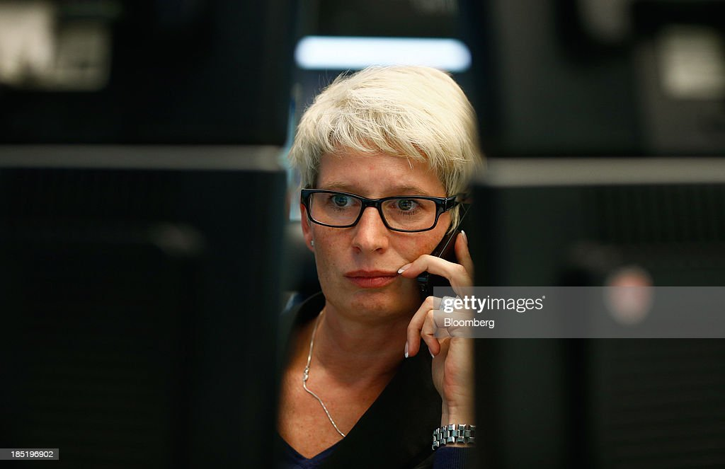 A financial trader uses a smartphone as she monitors data on her computer screens at the Frankfurt Stock Exchange in Frankfurt, Germany, on Friday, Oct. 18, 2013. Global stocks rose for a third day, extending a five-year high, and copper climbed after China's economic growth quickened. Photographer: Ralph Orlowski/Bloomberg via Getty Images