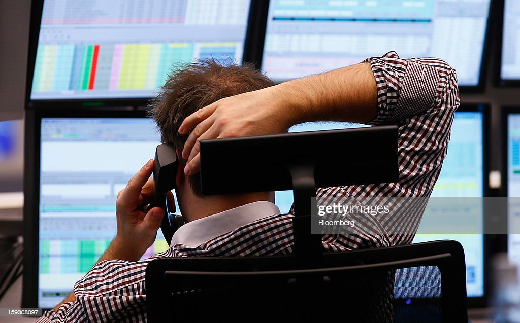 A financial trader uses a telephone as he monitors data on his computer screens at the Frankfurt Stock Exchange in Frankfurt, Germany, on Friday, Jan. 11. 2013. European stocks pared their decline as Italy's borrowing costs dropped at a debt sale, offsetting concern that China has less room for monetary easing after a reported showed inflation increased more than estimated. Photographer: Ralph Orlowski/Bloomberg via Getty Images