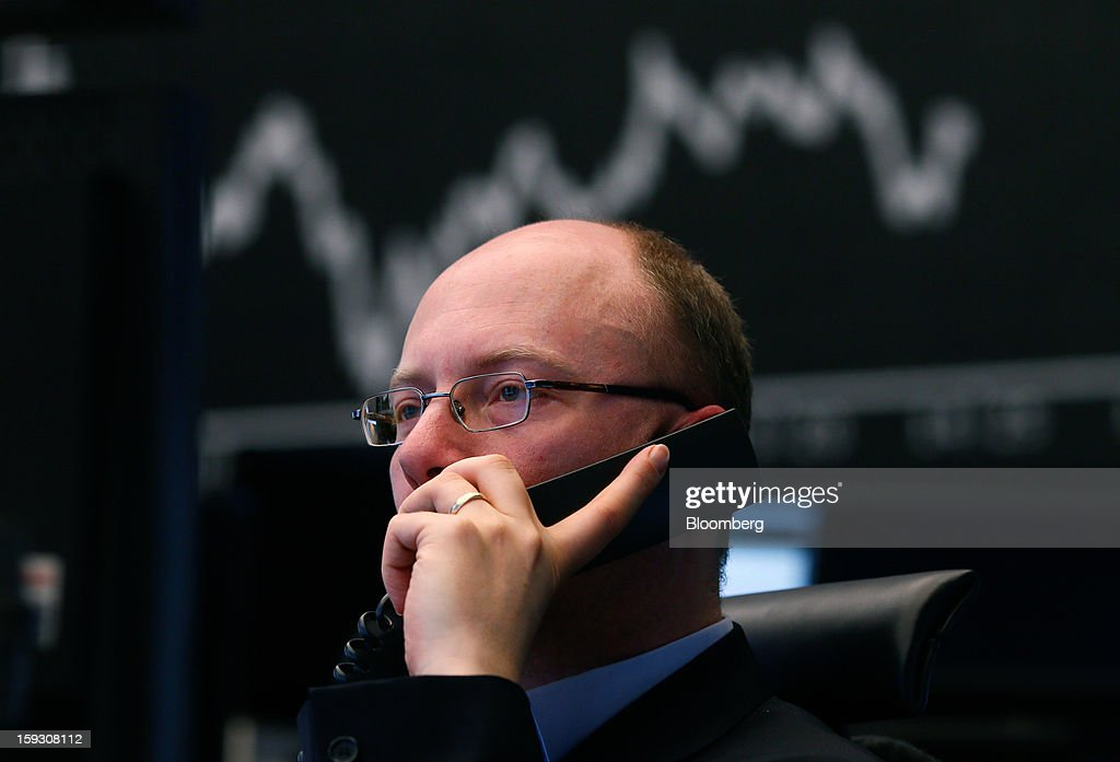 A financial trader uses a telephone as he monitors data on his computer screens in front of a display of the DAX Index curve at the Frankfurt Stock Exchange in Frankfurt, Germany, on Friday, Jan. 11. 2013. European stocks pared their decline as Italy's borrowing costs dropped at a debt sale, offsetting concern that China has less room for monetary easing after a reported showed inflation increased more than estimated. Photographer: Ralph Orlowski/Bloomberg via Getty Images