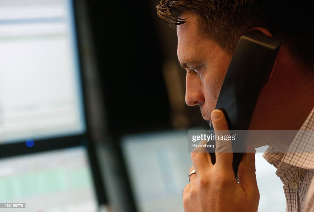 A financial trader uses a telephone as he monitors data on his computer screens at the Frankfurt Stock Exchange in Frankfurt, Germany, on Friday, Oct. 18, 2013. Global stocks rose for a third day, extending a five-year high, and copper climbed after China's economic growth quickened. Photographer: Ralph Orlowski/Bloomberg via Getty Images