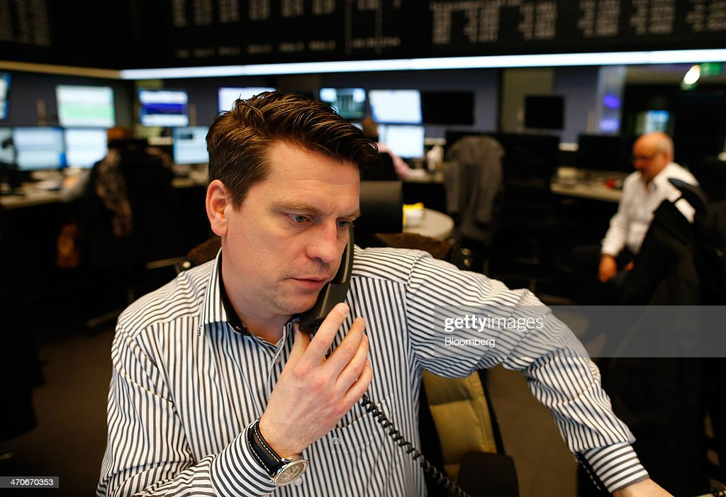 A financial trader uses a telephone as he works at the Frankfurt Stock Exchange in Frankfurt, Germany, on Thursday, Feb. 20, 2014. Deutsche Boerse AG plans to set up a clearinghouse in Singapore to compete with Singapore Exchange Ltd. and IntercontinentalExchange Group Inc. as the owner of the Frankfurt Stock Exchange and the Eurex futures market seeks to benefit from new financial regulations. Photographer: Ralph Orlowski/Bloomberg via Getty Images