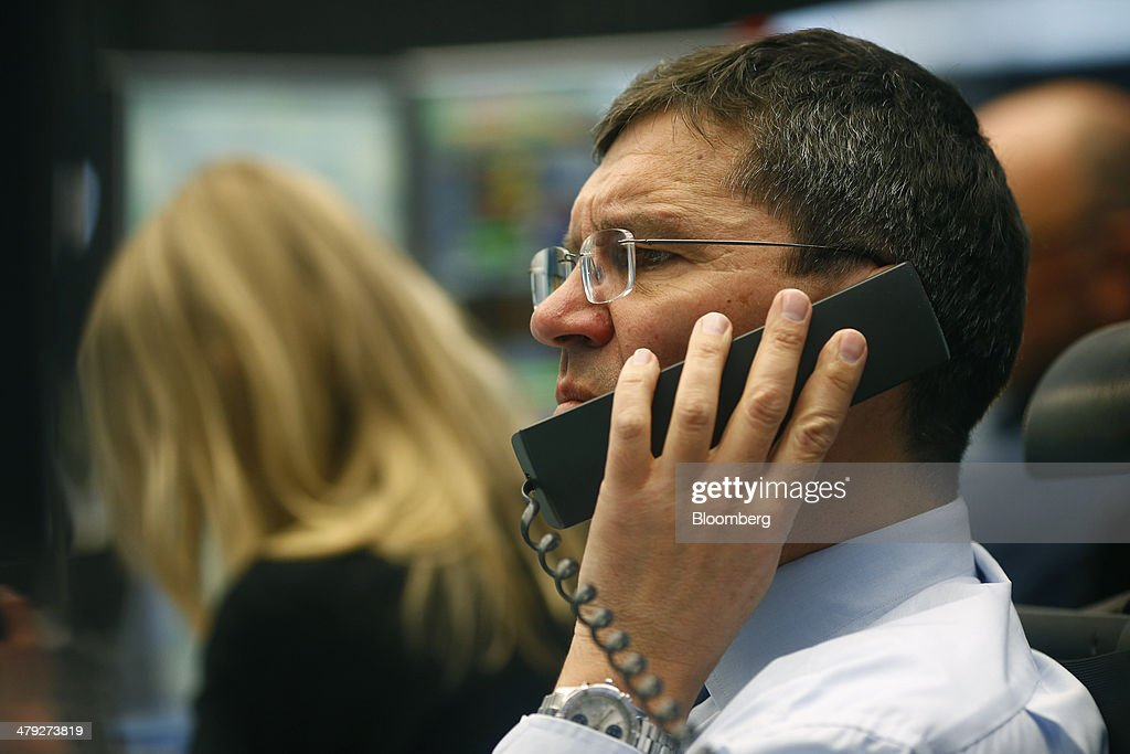 A financial trader uses a telephone as he works at the Frankfurt Stock Exchange in Frankfurt, Germany, on Monday, March 17, 2014. European stocks advanced, following their biggest weekly drop since January, as companies from RWE AG to Vodafone Group Plc rose amid renewed merger-and-acquisition activity. Photographer: Ralph Orlowski/Bloomberg via Getty Images