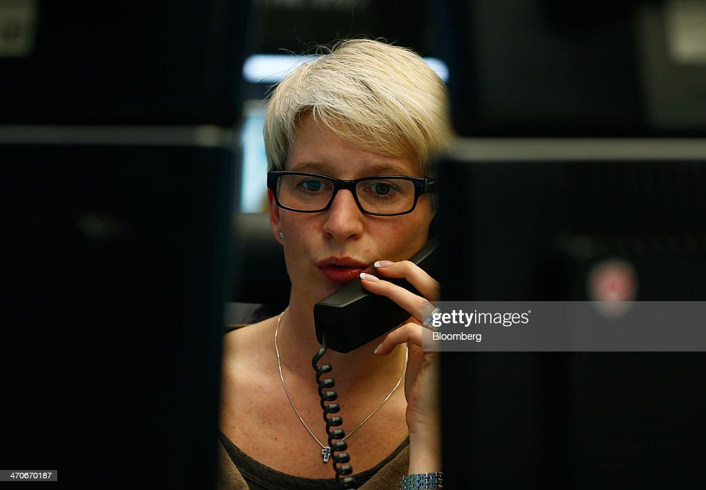 A financial trader uses a telephone as she monitors data on her computer screens at the Frankfurt Stock Exchange in Frankfurt, Germany, on Thursday, Feb. 20, 2014. Deutsche Boerse AG plans to set up a clearinghouse in Singapore to compete with Singapore Exchange Ltd. and IntercontinentalExchange Group Inc. as the owner of the Frankfurt Stock Exchange and the Eurex futures market seeks to benefit from new financial regulations. Photographer: Ralph Orlowski/Bloomberg via Getty Images