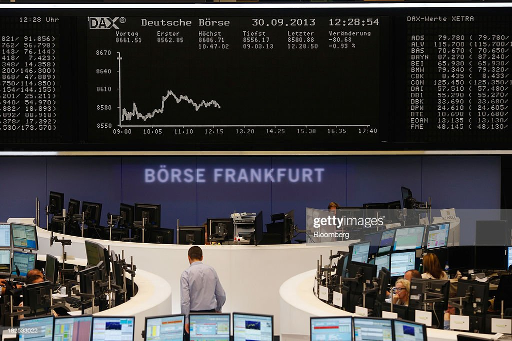 A financial trader walks across the trading floor below a display of the DAX Index curve at the Frankfurt Stock Exchange in Frankfurt, Germany, on Monday, Sept. 30, 2013. Global stocks fell, trimming their biggest quarterly gain since the start of 2012, while the Japanese yen strenghtened before a potential U.S. government shutdown. Photographer: Ralph Orlowski/Bloomberg via Getty Images
