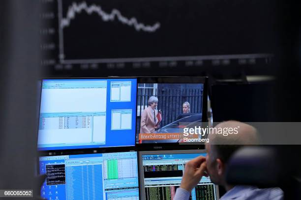 A financial trader watches a television news broadcast reporting on the UK triggering Article 50 of the Lisbon Treaty as the stock index curve sits...